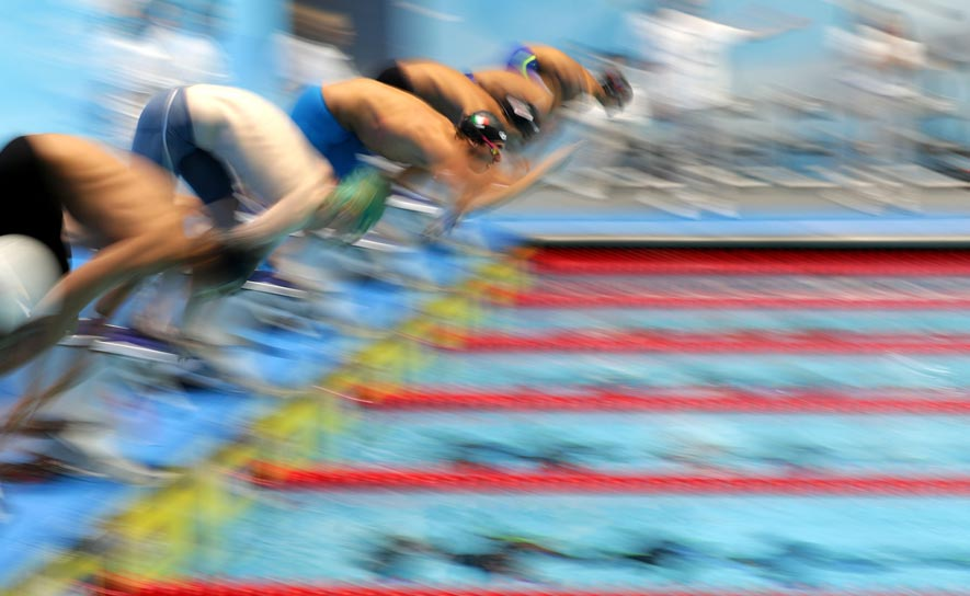 Blurred swimmers at the start of a race at the FINA World Junior Swimming Championships